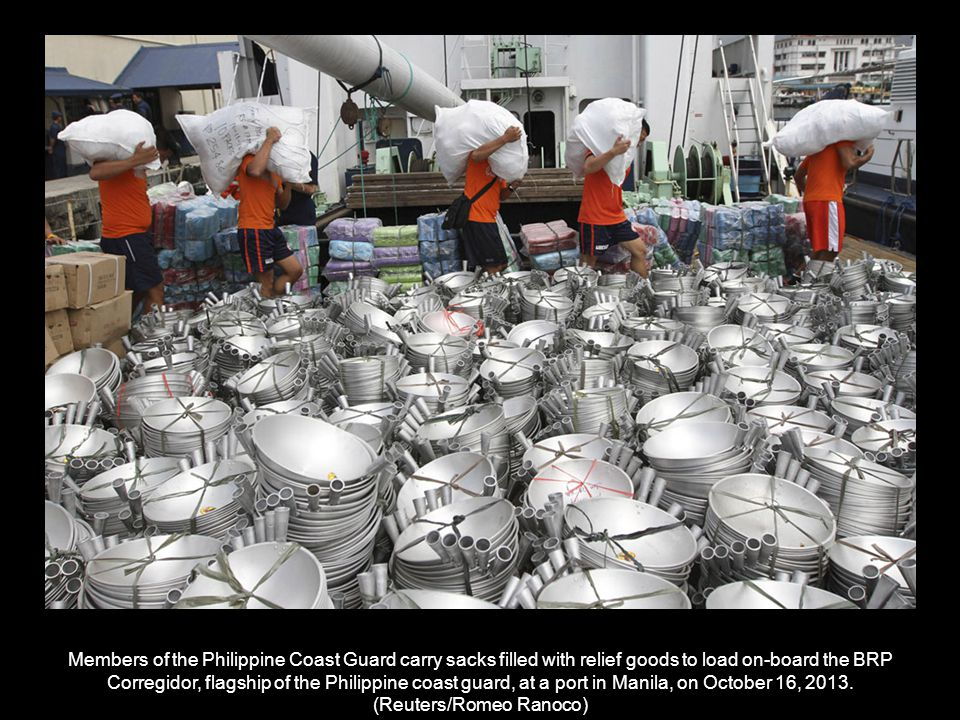 Philippine Coast Guard (PCG) personnel load relief goods onto a PCG vessel at a port in Manila on October 16, 2013.