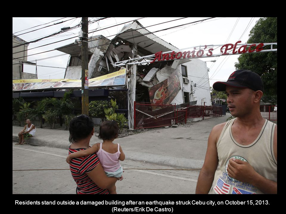 Residents walk past a destroyed church belfry in Tubigon, Bohol, on October 16, 2013.