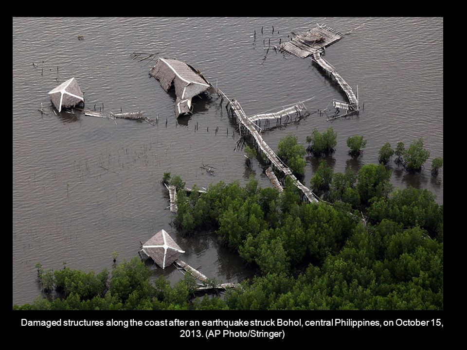 Villagers use a boat to cross a river after a bridge was damaged in Loon, Bohol, on October 16, 2013.