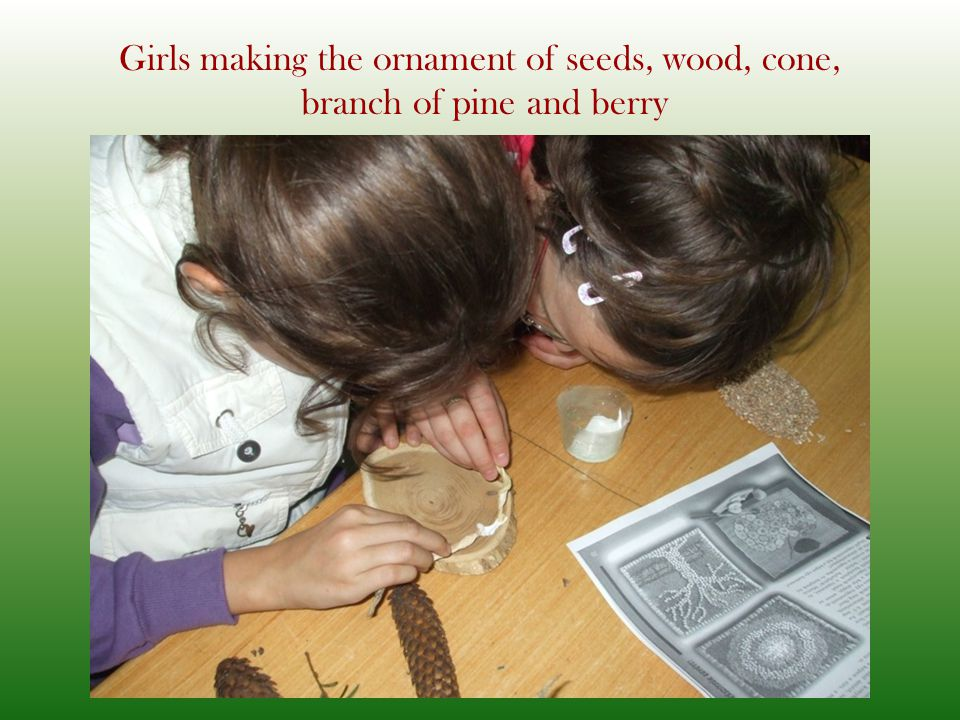 Girls making the ornament of seeds, wood, cone, branch of pine and berry