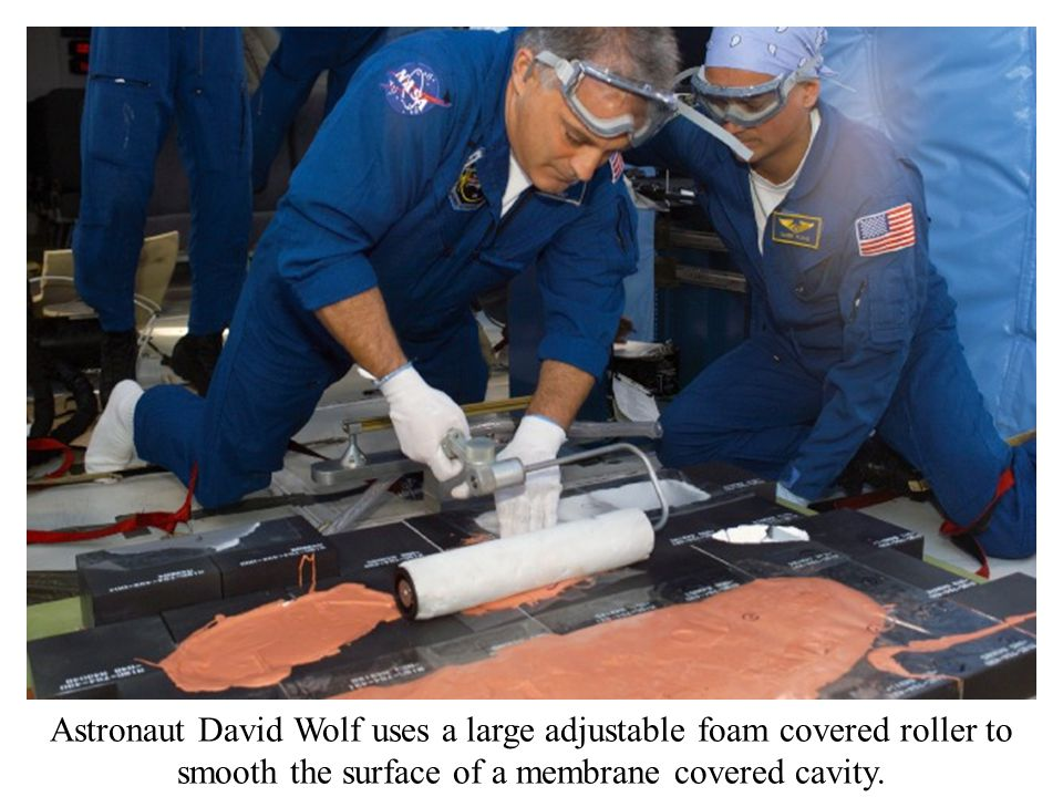 Astronaut David Wolf uses a large adjustable foam covered roller to smooth the surface of a membrane covered cavity.