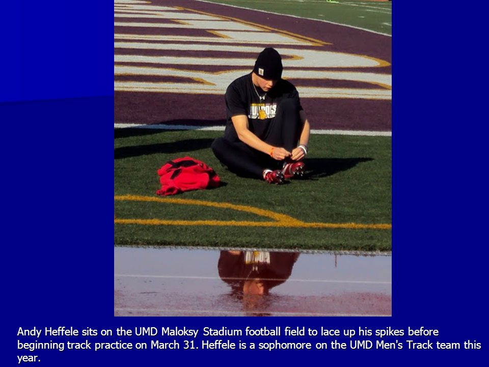 Andy Heffele sits on the UMD Maloksy Stadium football field to lace up his spikes before beginning track practice on March 31. Heffele is a sophomore