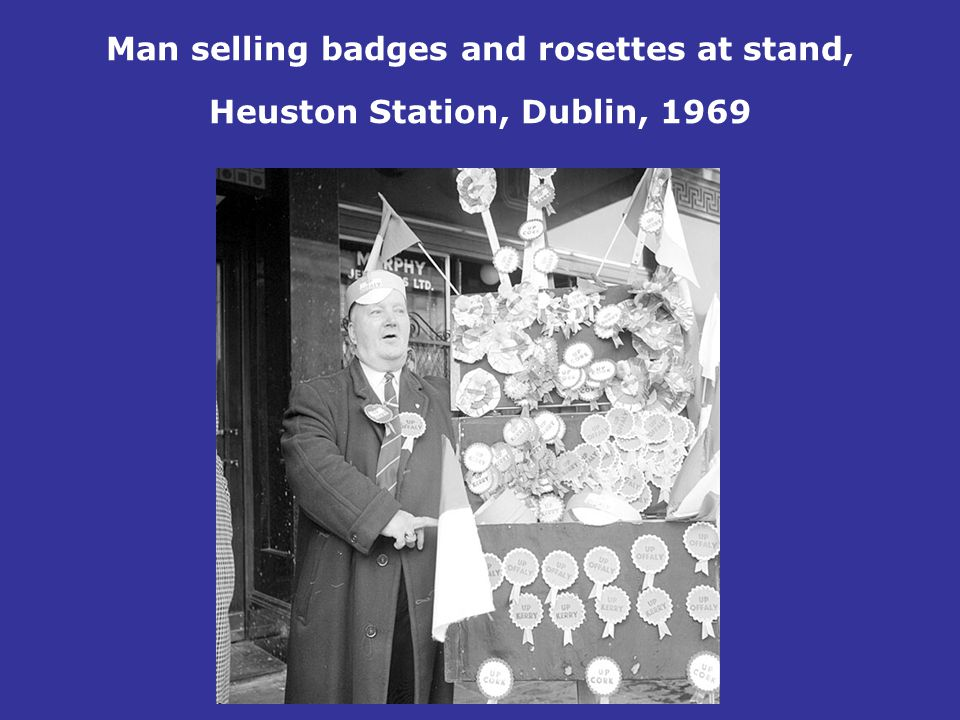 Man selling badges and rosettes at stand, Heuston Station, Dublin, 1969