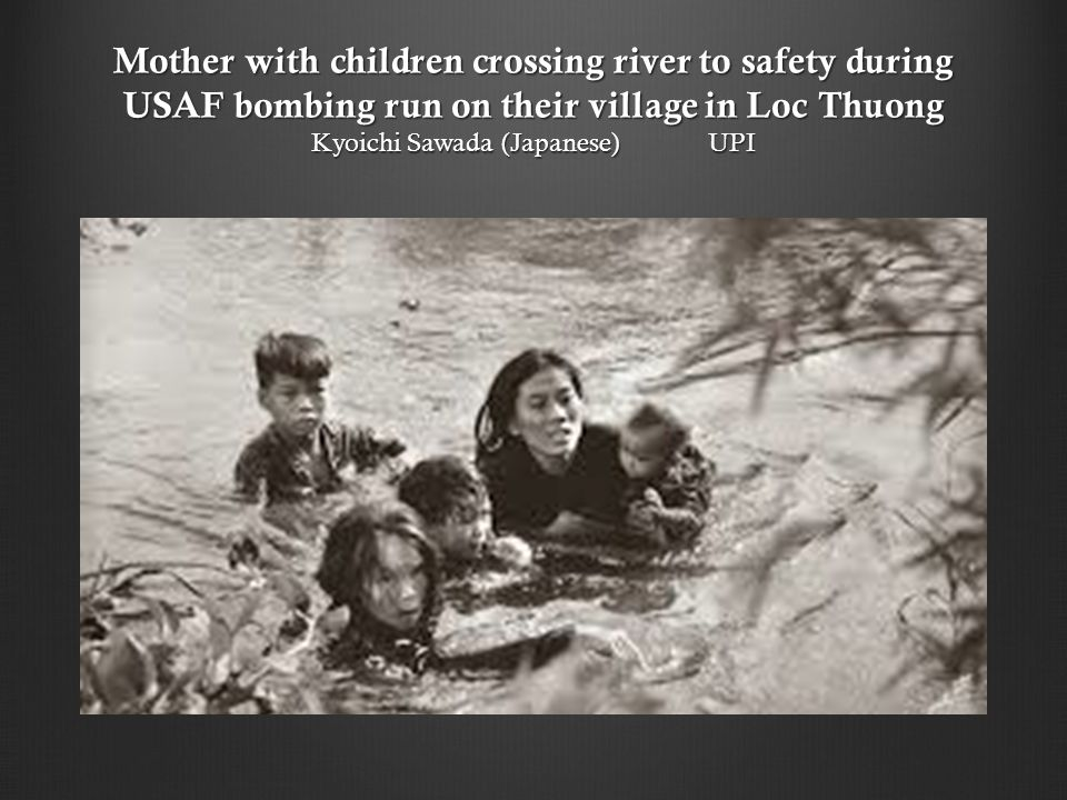 Mother with children crossing river to safety during USAF bombing run on their village in Loc Thuong Kyoichi Sawada (Japanese) UPI