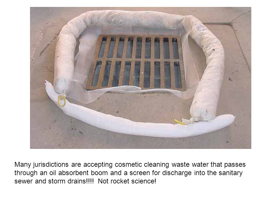 The storm drain is sealed, waste water passes through an oil absorbent boom for removal of hydrocarbons and a window screen (around the bottom of the