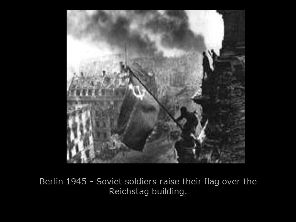 Berlin 1945 - Soviet soldiers raise their flag over the Reichstag building.