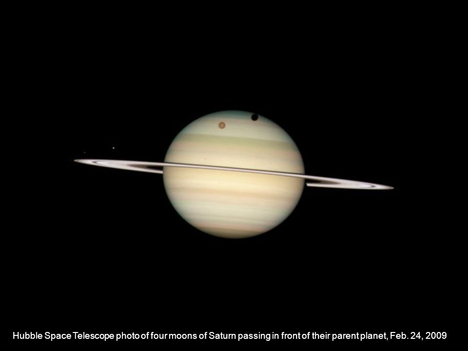 Hubble Space Telescope photo of four moons of Saturn passing in front of their parent planet, Feb. 24, 2009