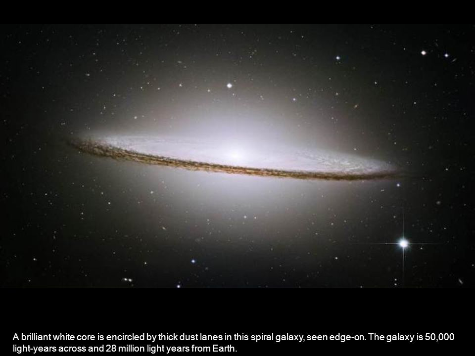 A brilliant white core is encircled by thick dust lanes in this spiral galaxy, seen edge-on. The galaxy is 50,000 light-years across and 28 million li