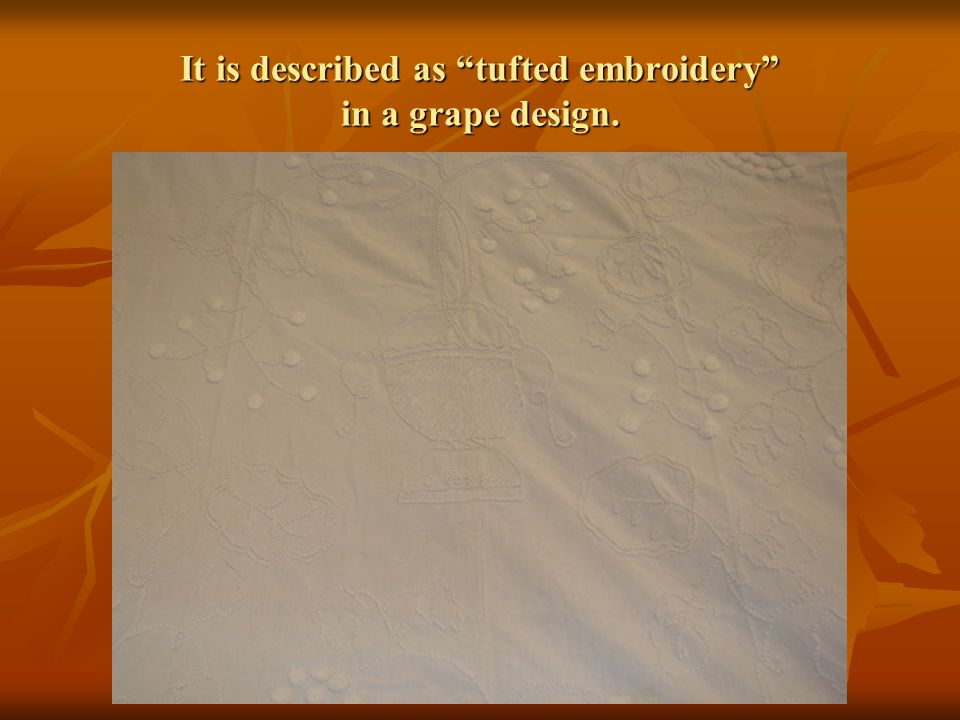 It is described as tufted embroidery in a grape design.