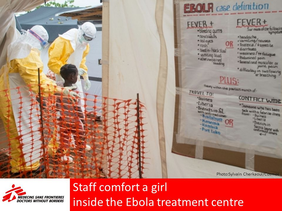 Staff comfort a girl inside the Ebola treatment centre Photo:Sylvain Cherkaoui/Cosmos