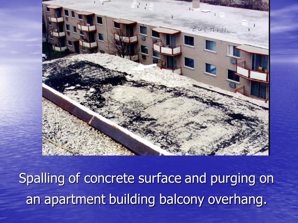Spalling of concrete surface and purging on an apartment building balcony overhang.