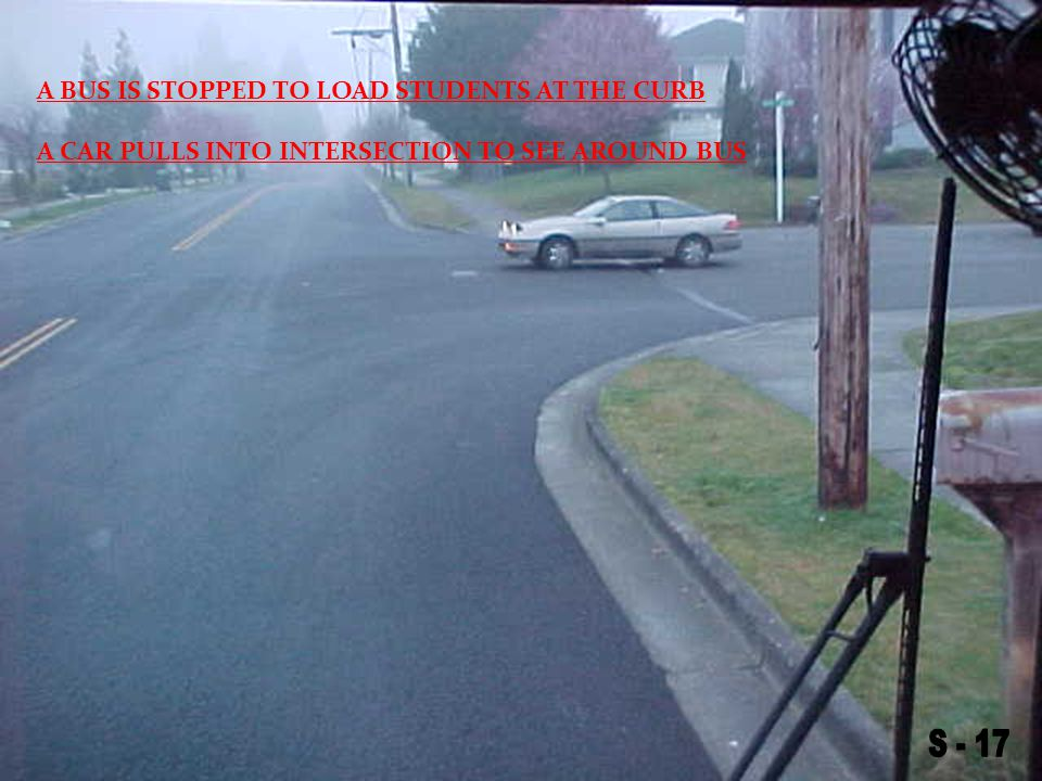 A CAR PULLS INTO INTERSECTION TO SEE AROUND BUS A BUS IS STOPPED TO LOAD STUDENTS AT THE CURB