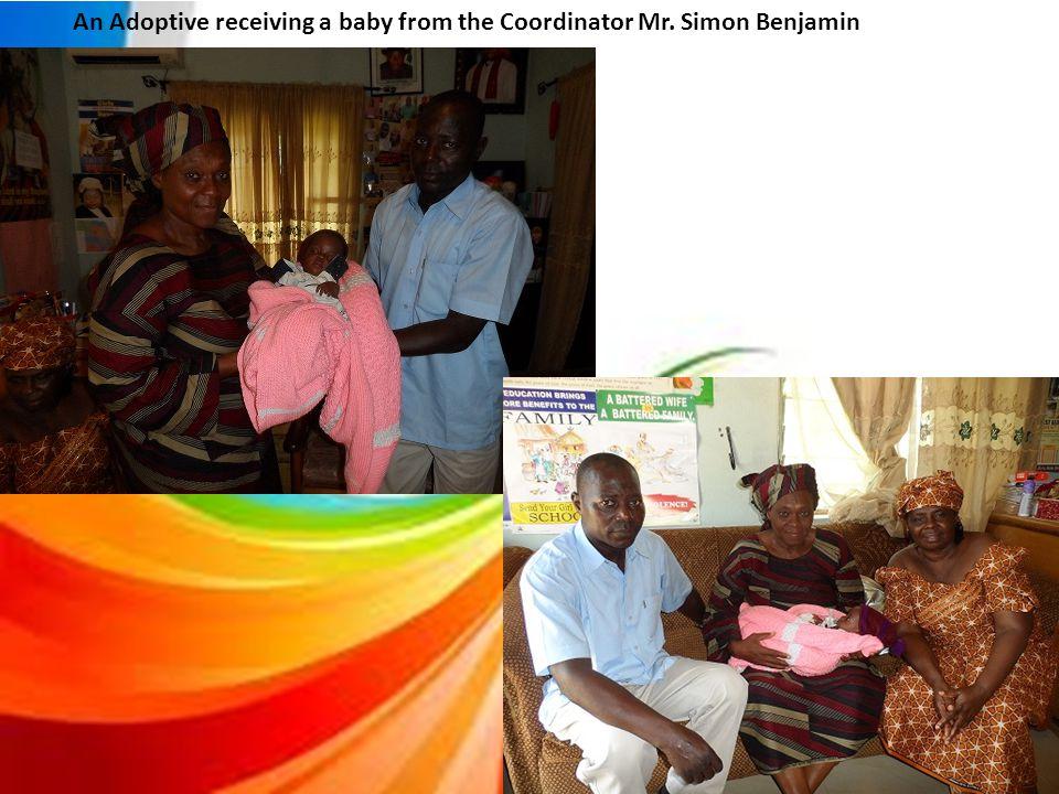 An Adoptive receiving a baby from the Coordinator Mr. Simon Benjamin