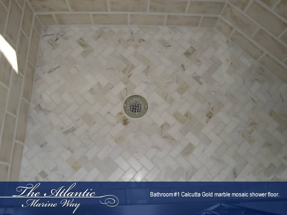 Bathroom #1 Calcutta Gold marble mosaic shower floor.