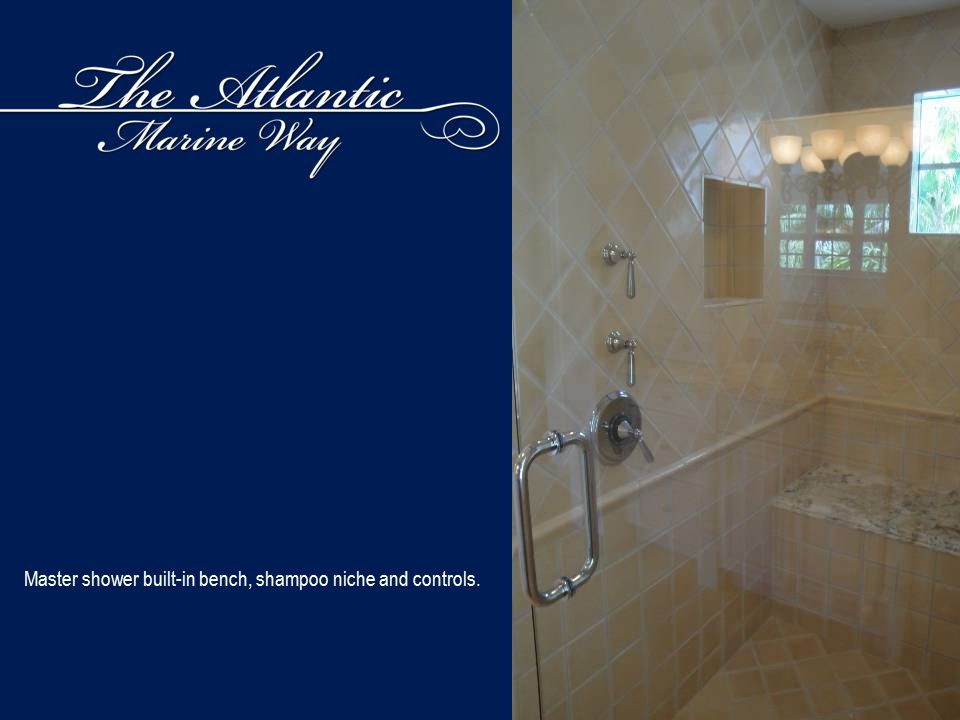 Master shower built-in bench, shampoo niche and controls.
