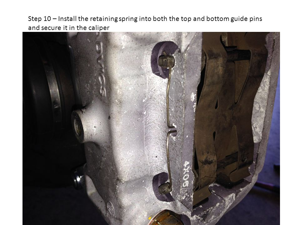 Step 10 – Install the retaining spring into both the top and bottom guide pins and secure it in the caliper