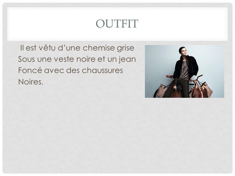 OUTFIT Il est vêtu d'une chemise grise Sous une veste noire et un jean Foncé avec des chaussures Noires.