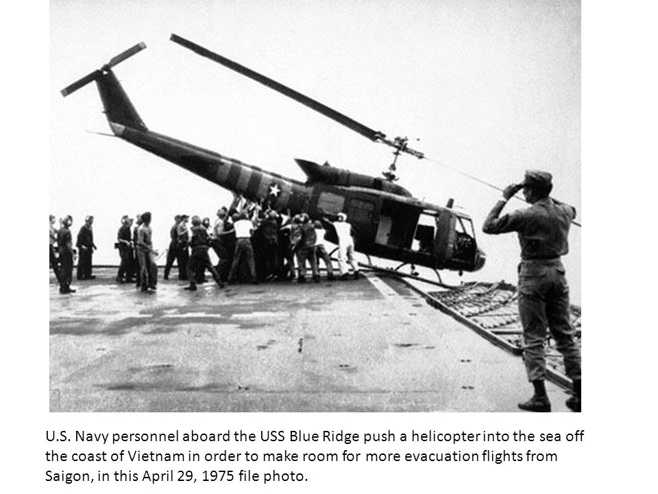 U.S. Navy personnel aboard the USS Blue Ridge push a helicopter into the sea off the coast of Vietnam in order to make room for more evacuation flight