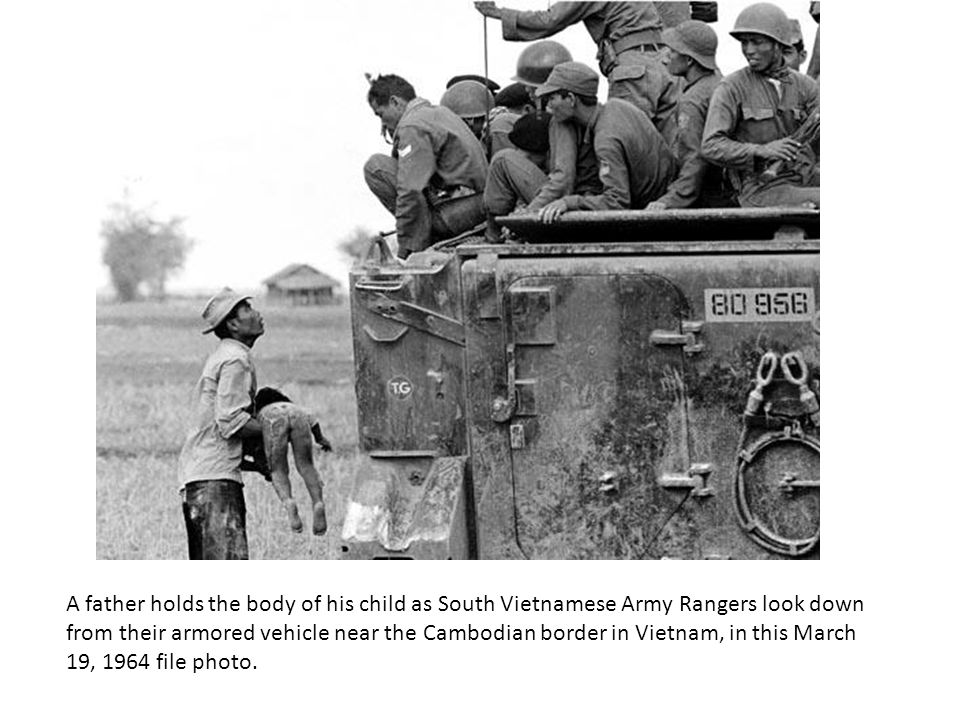 A father holds the body of his child as South Vietnamese Army Rangers look down from their armored vehicle near the Cambodian border in Vietnam, in this March 19, 1964 file photo.