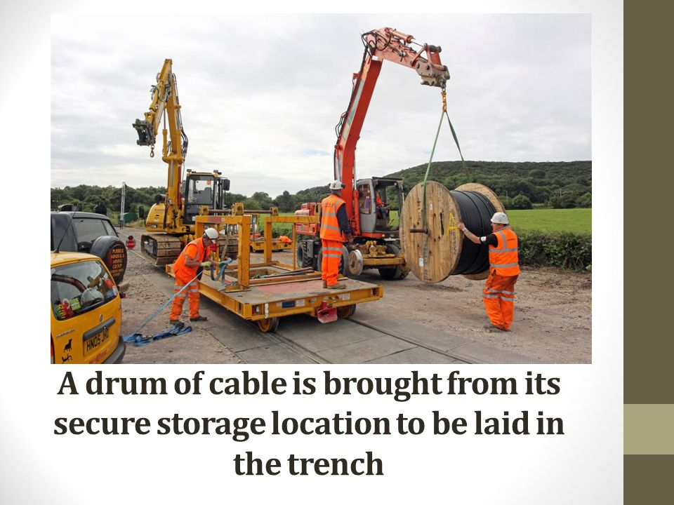 A drum of cable is brought from its secure storage location to be laid in the trench