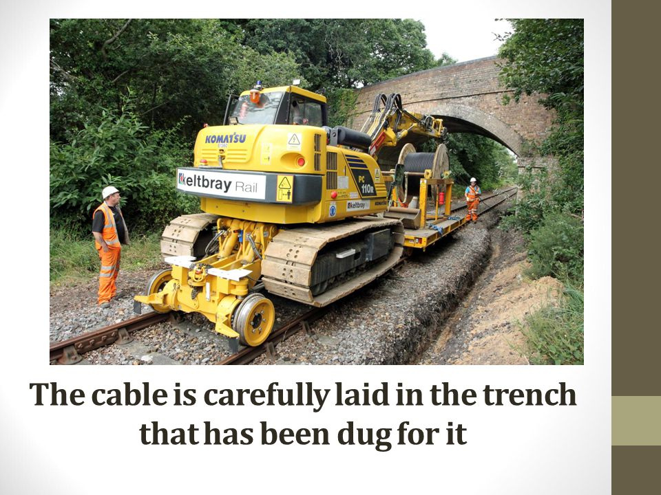 The cable is carefully laid in the trench that has been dug for it