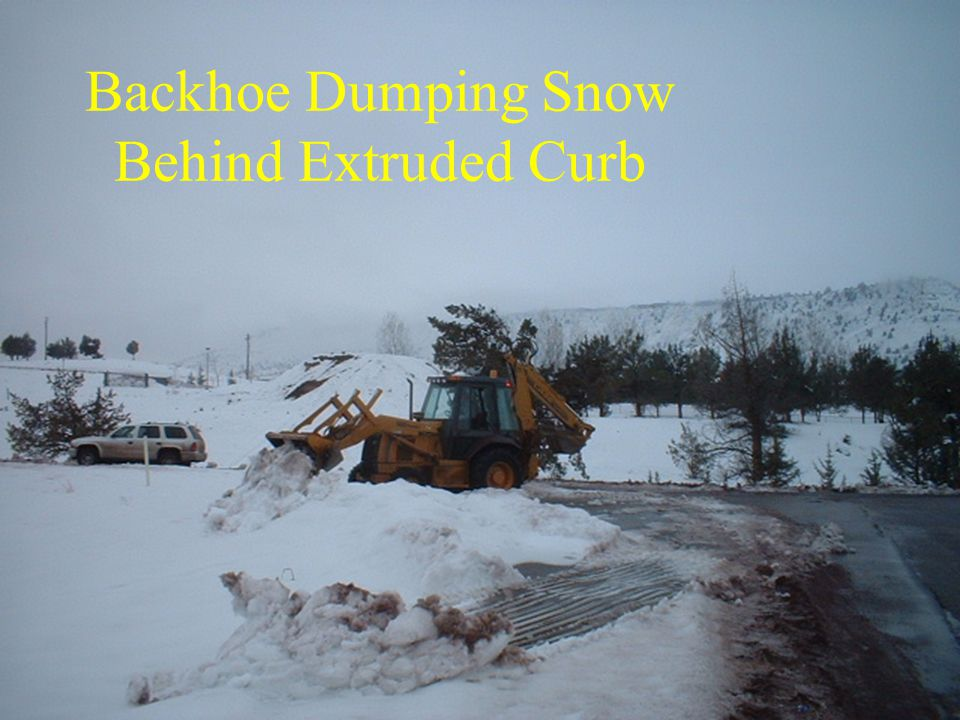 Backhoe Dumping Snow Behind Extruded Curb