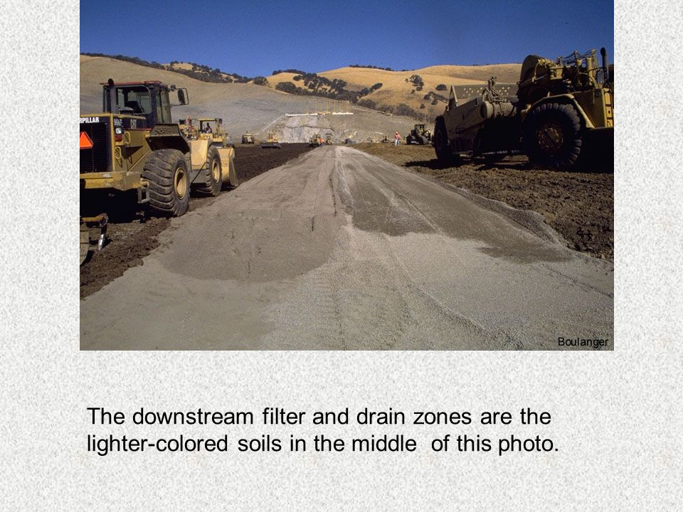 The downstream filter and drain zones are the lighter-colored soils in the middle of this photo.