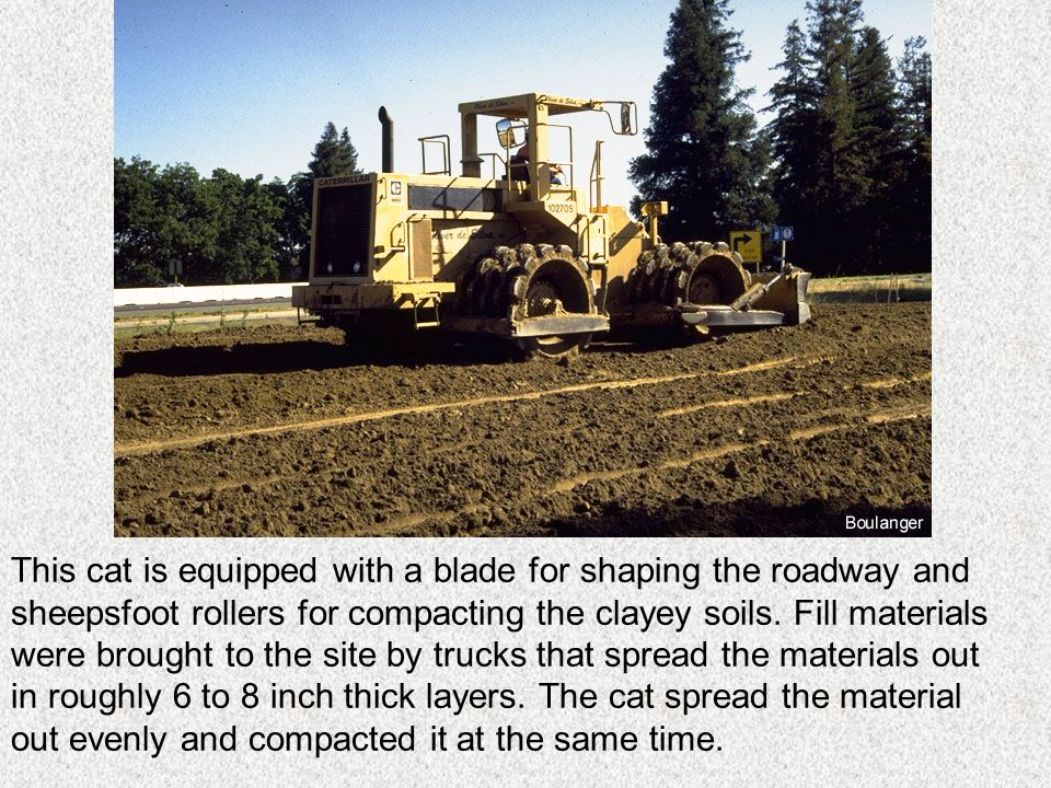 This cat is equipped with a blade for shaping the roadway and sheepsfoot rollers for compacting the clayey soils.