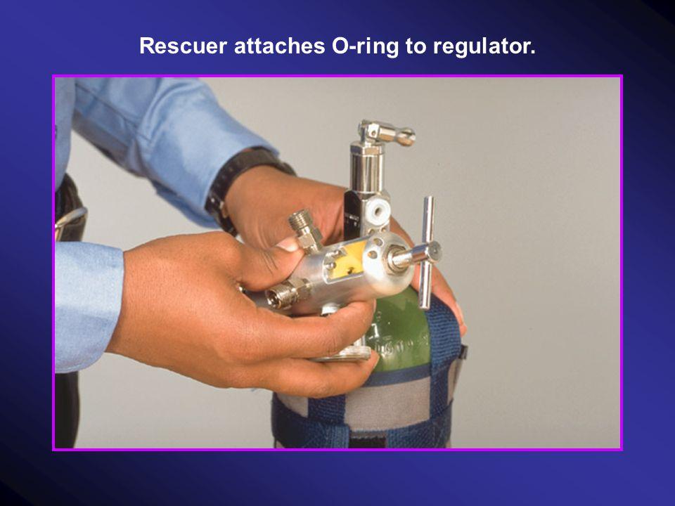 Rescuer attaches regulator to cylinder.