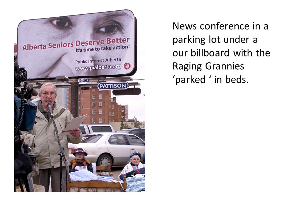 News conference in a parking lot under a our billboard with the Raging Grannies 'parked ' in beds.