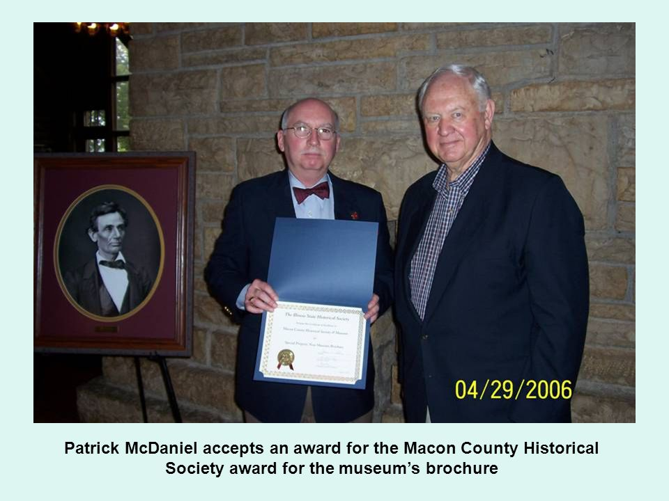 Patrick McDaniel accepts an award for the Macon County Historical Society award for the museum's brochure