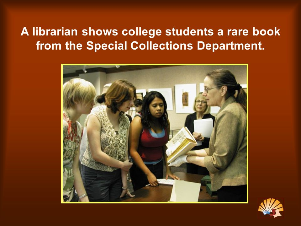 A librarian shows college students a rare book from the Special Collections Department.