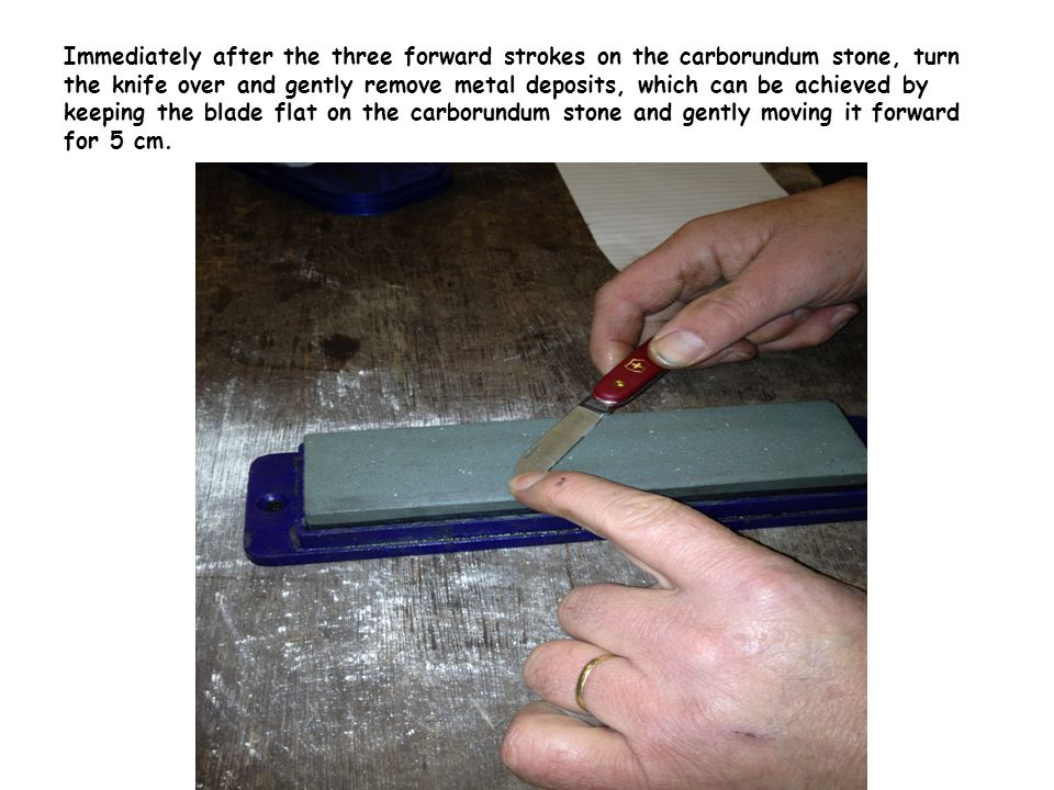 Immediately after the three forward strokes on the carborundum stone, turn the knife over and gently remove metal deposits, which can be achieved by keeping the blade flat on the carborundum stone and gently moving it forward for 5 cm.