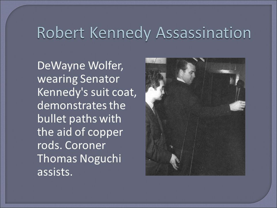DeWayne Wolfer, wearing Senator Kennedy s suit coat, demonstrates the bullet paths with the aid of copper rods.
