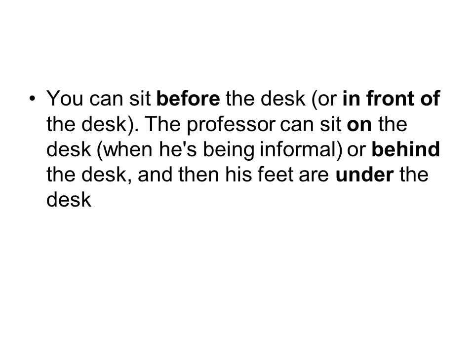 You can sit before the desk (or in front of the desk). The professor can sit on the desk (when he's being informal) or behind the desk, and then his f