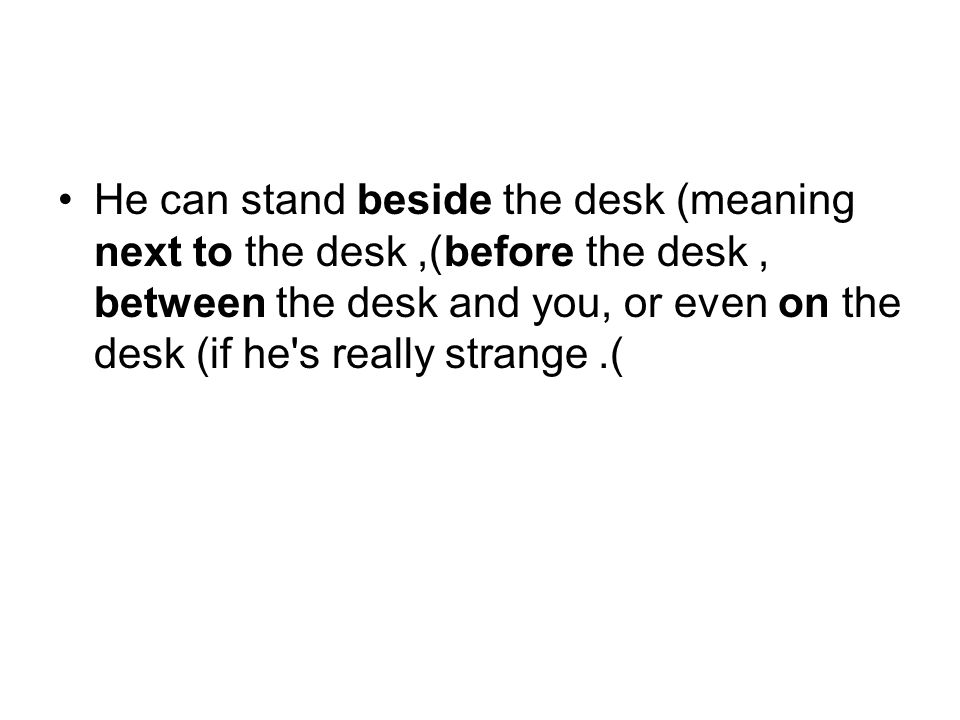 He can stand beside the desk (meaning next to the desk), before the desk, between the desk and you, or even on the desk (if he's really strange).