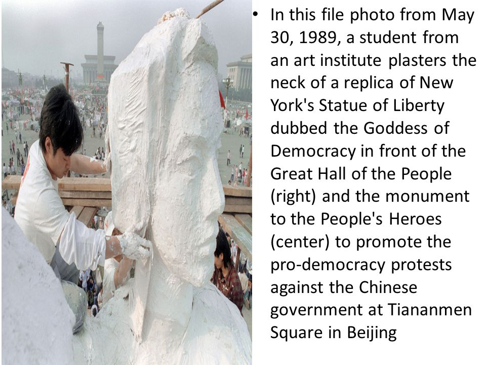 In this file photo from May 30, 1989, a student from an art institute plasters the neck of a replica of New York s Statue of Liberty dubbed the Goddess of Democracy in front of the Great Hall of the People (right) and the monument to the People s Heroes (center) to promote the pro-democracy protests against the Chinese government at Tiananmen Square in Beijing