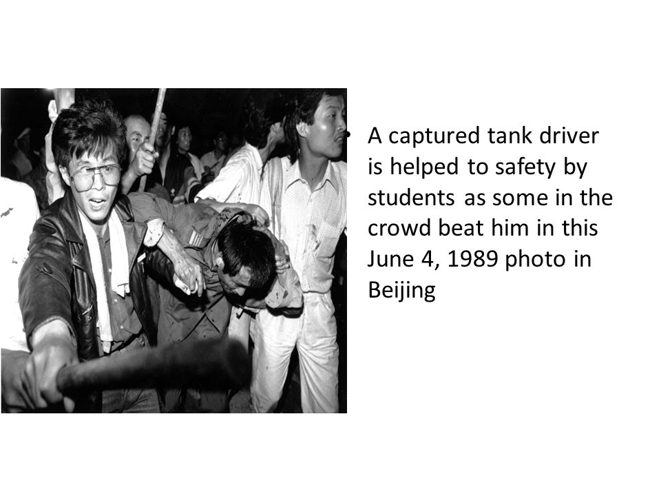 A captured tank driver is helped to safety by students as some in the crowd beat him in this June 4, 1989 photo in Beijing