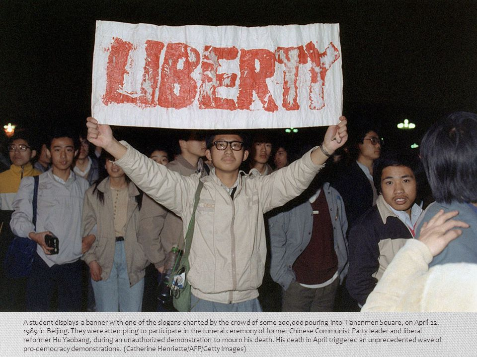 A student displays a banner with one of the slogans chanted by the crowd of some 200,000 pouring into Tiananmen Square, on April 22, 1989 in Beijing.