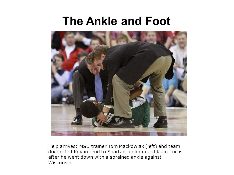 The Ankle and Foot Help arrives: MSU trainer Tom Mackowiak (left) and team doctor Jeff Kovan tend to Spartan junior guard Kalin Lucas after he went down with a sprained ankle against Wisconsin