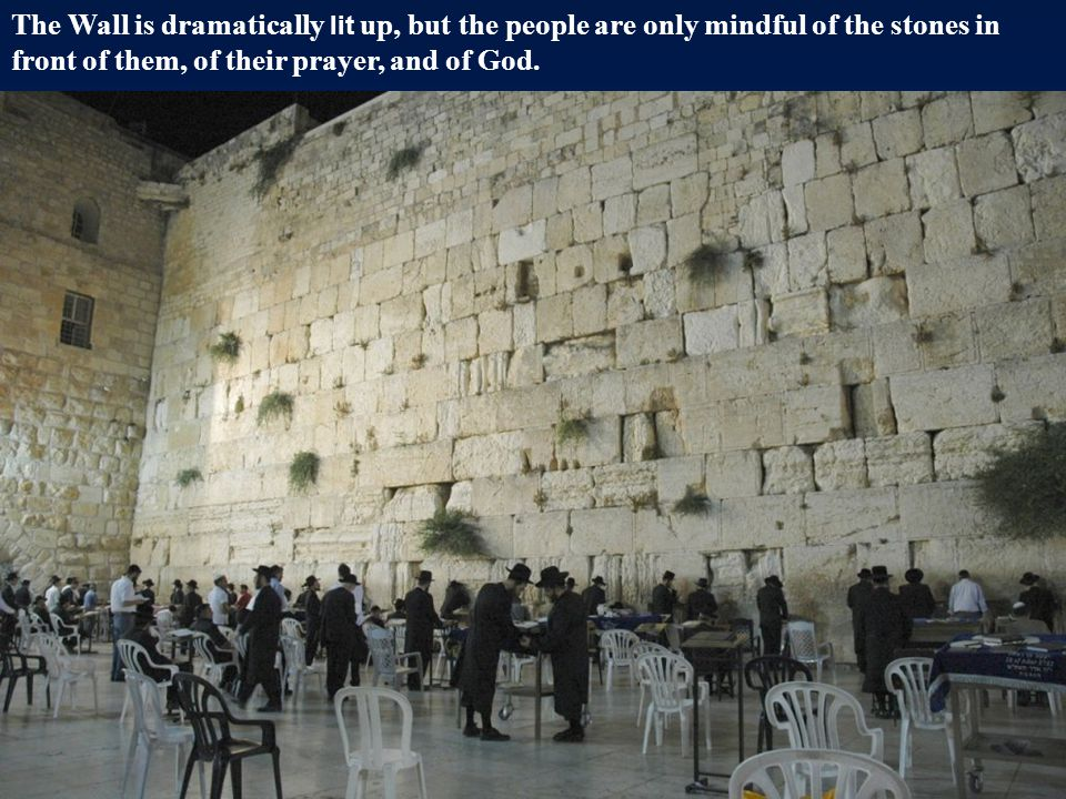 The Wall is dramatically lit up, but the people are only mindful of the stones in front of them, of their prayer, and of God.