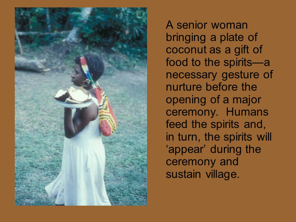 A senior woman bringing a plate of coconut as a gift of food to the spirits—a necessary gesture of nurture before the opening of a major ceremony. Hum