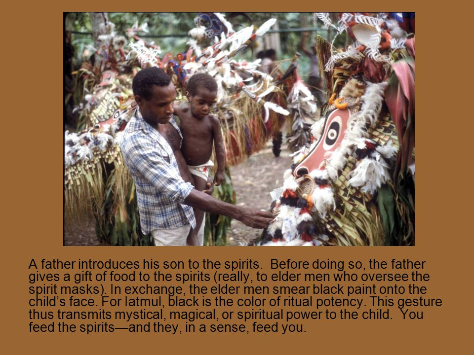 A father introduces his son to the spirits. Before doing so, the father gives a gift of food to the spirits (really, to elder men who oversee the spir