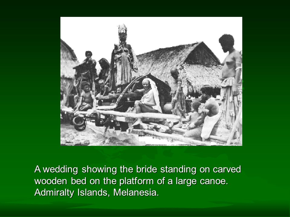 A wedding showing the bride standing on carved wooden bed on the platform of a large canoe.