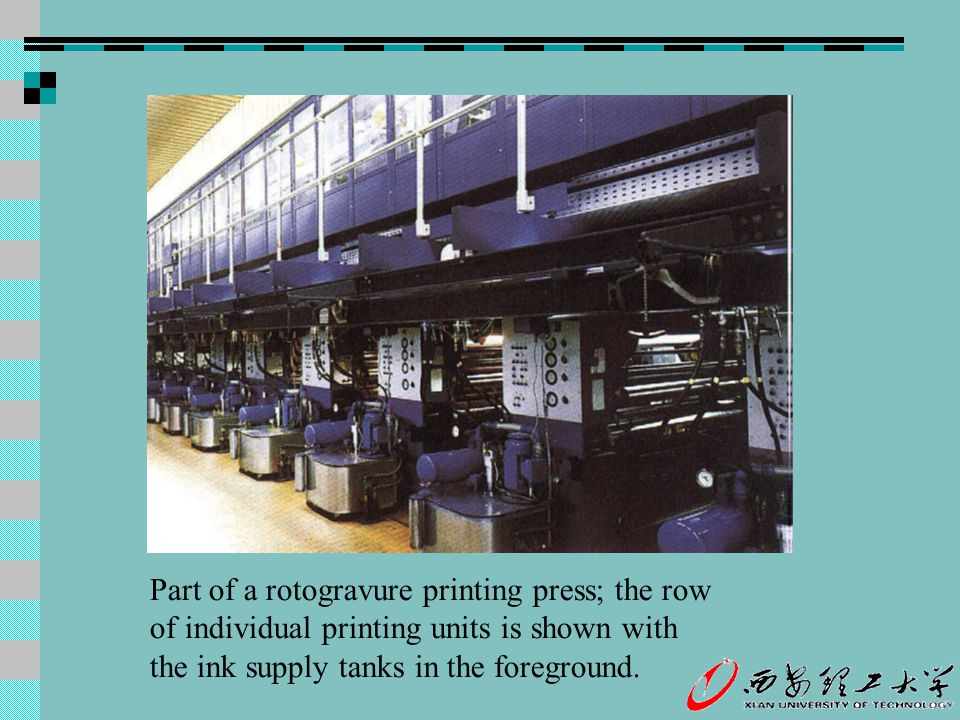 Part of a rotogravure printing press; the row of individual printing units is shown with the ink supply tanks in the foreground.