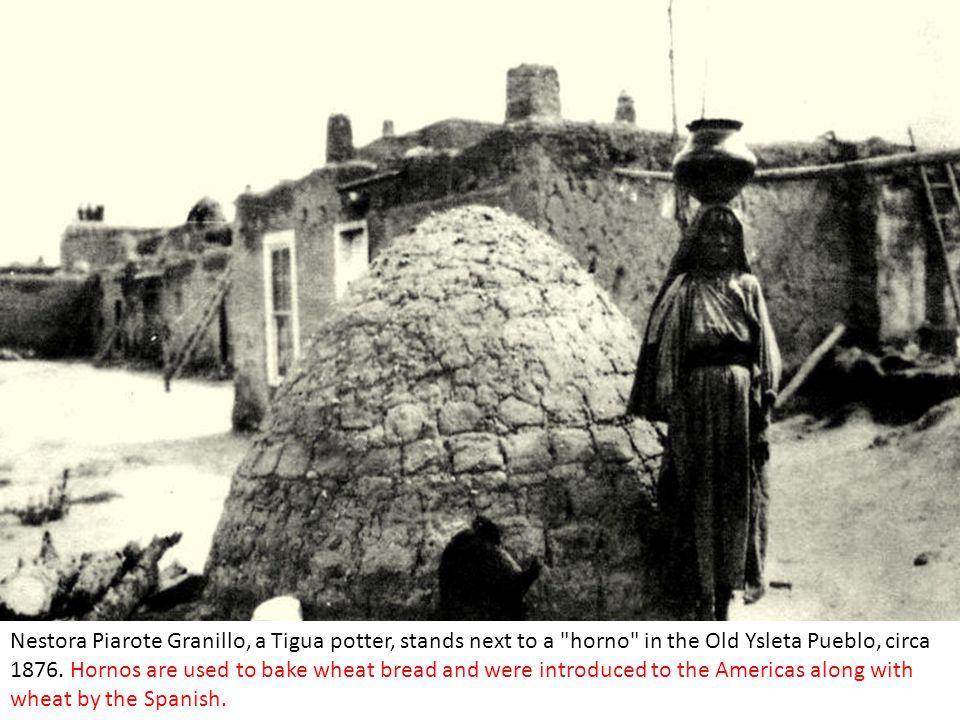 Nestora Piarote Granillo, a Tigua potter, stands next to a horno in the Old Ysleta Pueblo, circa 1876.