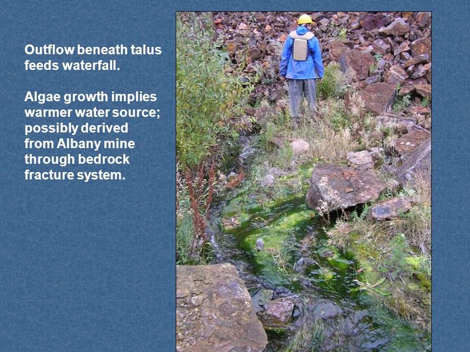 Outflow beneath talus feeds waterfall. Algae growth implies warmer water source; possibly derived from Albany mine through bedrock fracture system.
