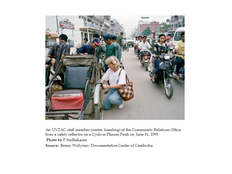 An UNTAC staff member (centre, kneeling) of the Community Relations Office fixes a safety reflector on a Cyclo in Phnom Penh on June 01, 1993 Photo by P Sudhakaran Source: Benny Widyono/Documentation Center of Cambodia