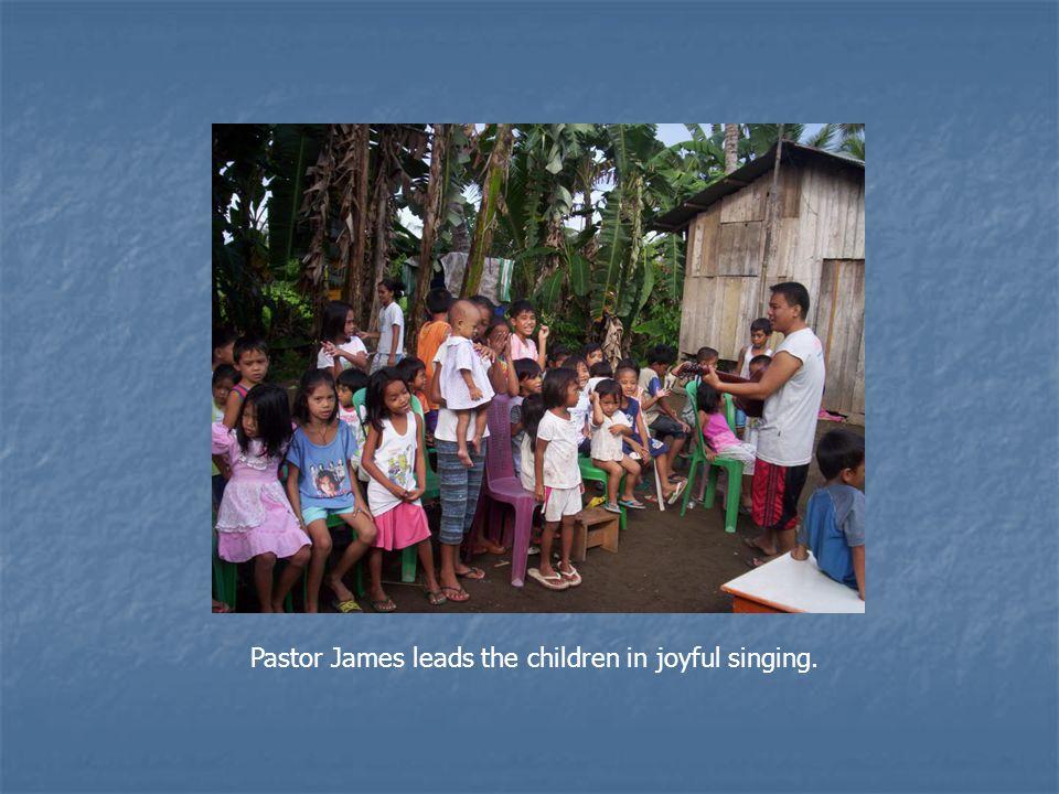 Pastor James leads the children in joyful singing.