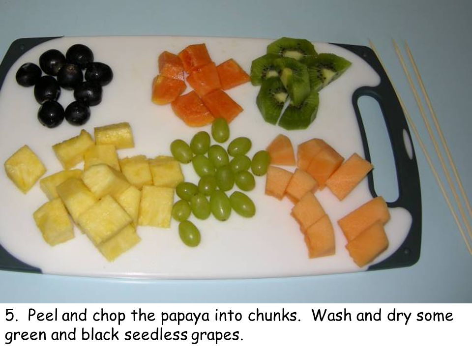 5. Peel and chop the papaya into chunks. Wash and dry some green and black seedless grapes.